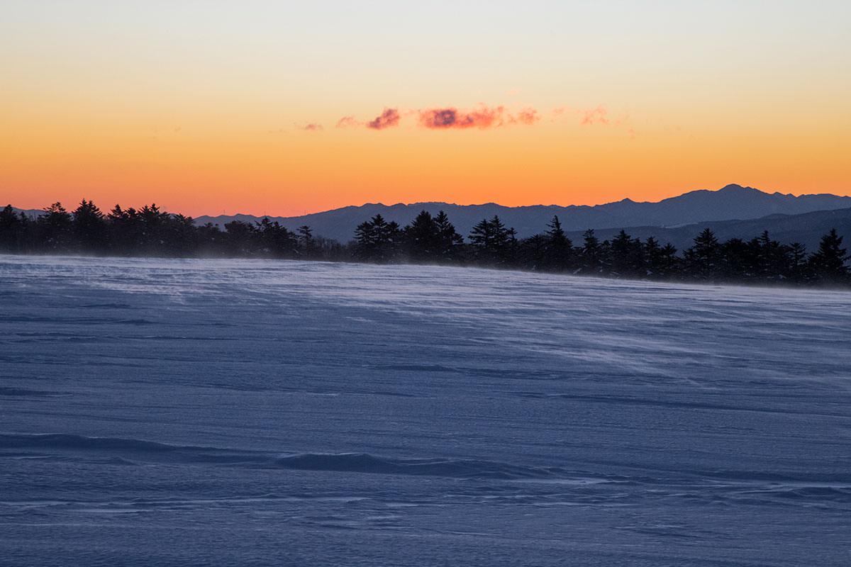 風が雪を巻き上げて朝陽の方へ流れて行く