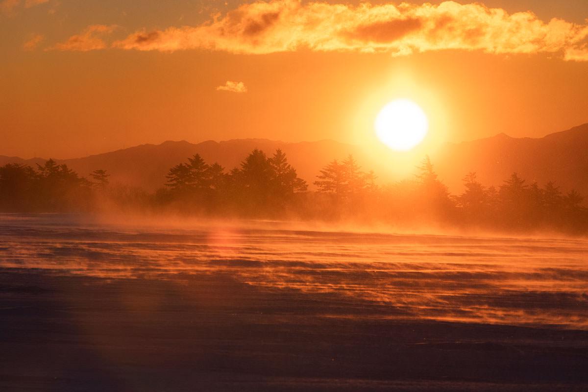 赤い朝陽に向かって雪が飛んでいく